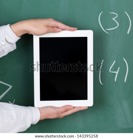 Teacher holding a tablet with a blank display in front of a blackboard with numbers written on it with chalk - stock photo