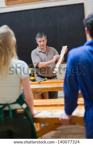 Teacher holding a wooden board while explaining something to his class - stock photo