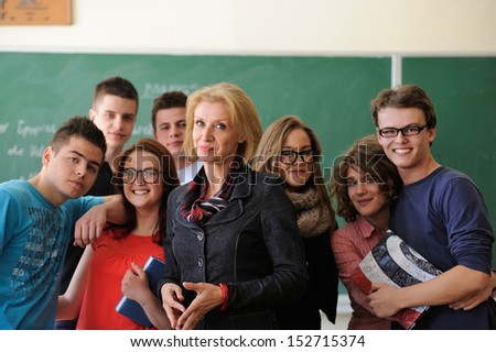 Teacher in a classroom surrounded by happy students - stock photo
