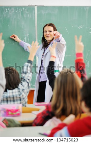 Teacher in classroom and looking at students who raised their arms