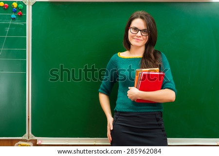 teacher in classroom near blackboard - stock photo