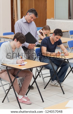 Teacher is standing next to the students at the classroom - stock photo