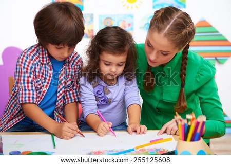 Teacher, little boy and a girl drawing something in preschool center for children - stock photo