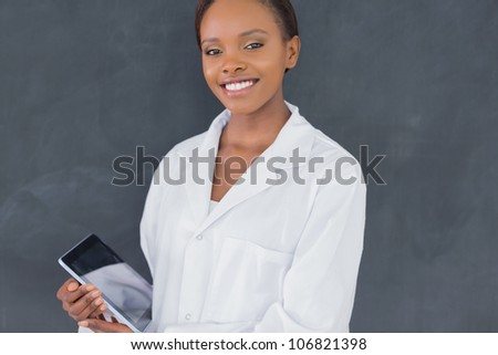 Teacher looking at camera while holding a tablet computer in a classroom