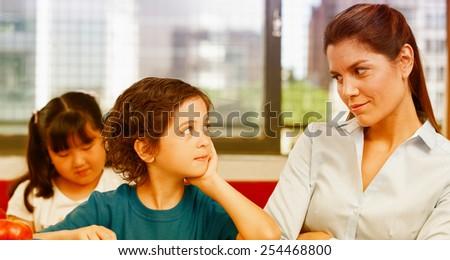 Teacher looking at kid with interrogative look. - stock photo