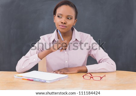 Teacher looking away while thinking in a class room - stock photo
