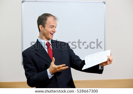 teacher man showing book beside table in classroom