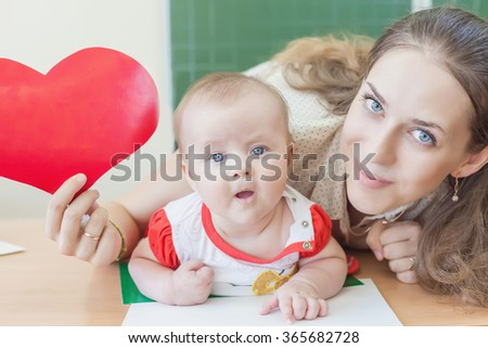 Teacher near blackboard teaching child, baby. Preschool, kindergarten, elementary. Holding a heart symbol. - stock photo