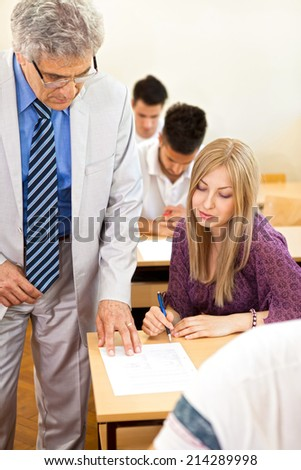 Teacher observes his  students class as they are taking a test. - stock photo