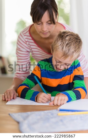 Teacher or concerned mother looking over the shoulder of a young boy as he sits at a table writing or drawing on a sheet of paper