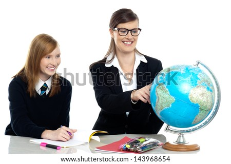 Teacher pointing out a country on the globe - stock photo