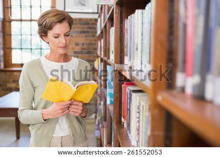 Teacher reading book at library at elementary school