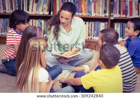 Teacher reading her pupils a story at the elementary school - stock photo