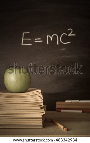 Teacher's desk with stack of exercise books, apple, pencil, duster and chalk.  E=mc2 formula on chalkboard to indicate genius or theoretical physics.  Faded colours for a retro or vintage effect.