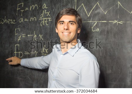 Teacher showing formulas on the blackboard - stock photo