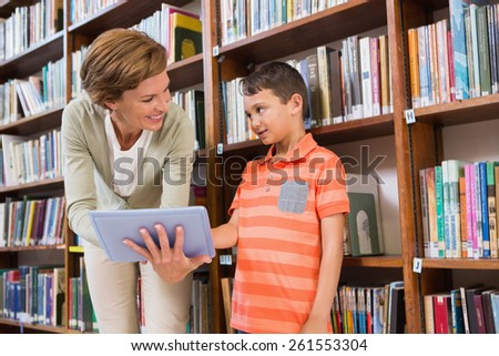 Teacher showing tablet to pupil at library at elementary school