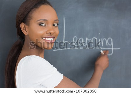 Teacher showing the blackboard while smiling in a classroom - stock photo