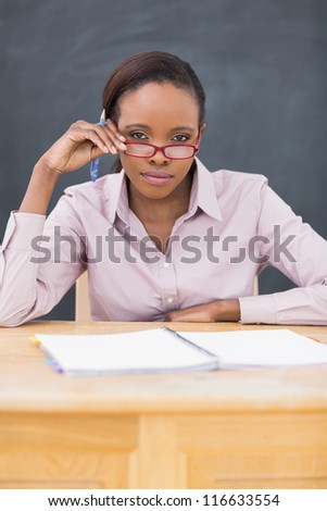 Teacher sitting at desk while touching her glasses in a classroom