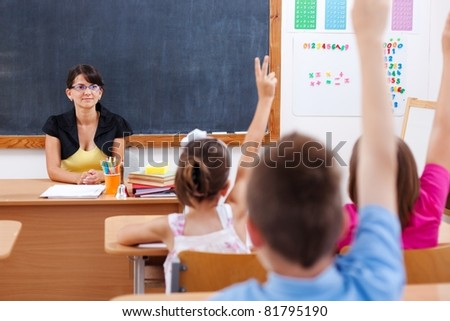 Teacher sitting in classroom and looking at students who raised their arms