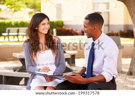 Teacher Sitting Outdoors Helping Female Student With Work
