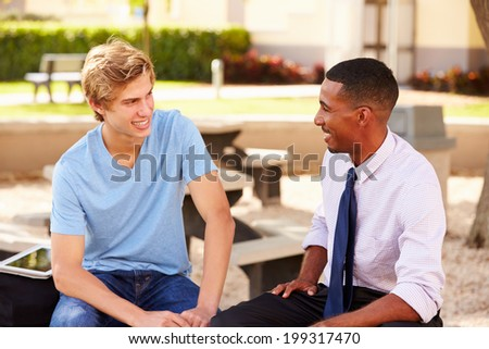 Teacher Sitting Talking To Male High School Student  Outside - stock photo