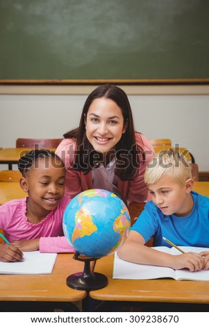 Teacher sitting with her students at the elementary school - stock photo