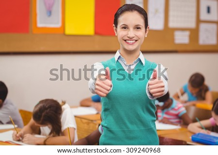 Teacher smiling at camera in classroom at the elementary school