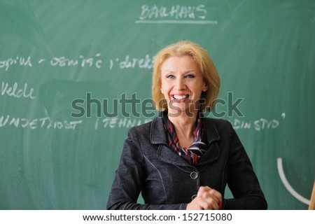 Teacher smiling in front of a chalkboard - stock photo