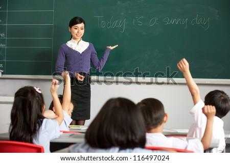 Teacher Standing By Blackboard In Chinese School Classroom - stock photo