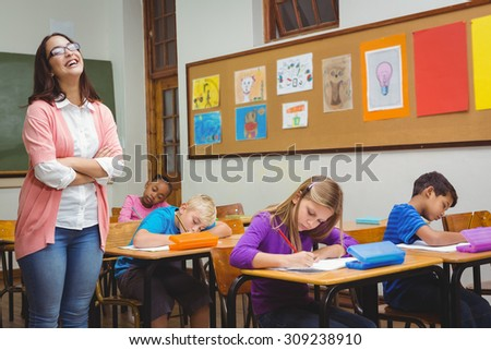 Teacher standing by her students at the elementary school - stock photo