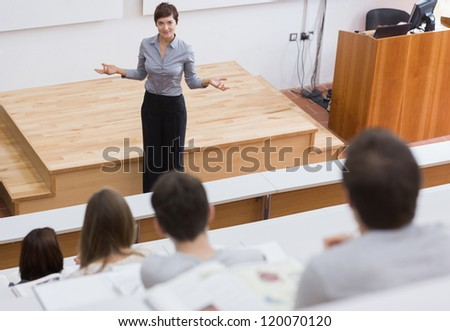 Teacher standing talking to the students at the lecture hall - stock photo
