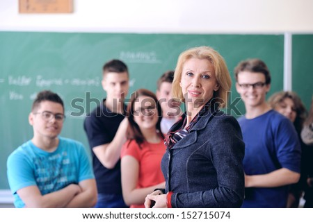 Teacher standing with her students in a background - stock photo