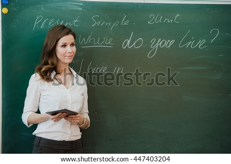 Teacher standing with tablet pc in classroom at elementary school