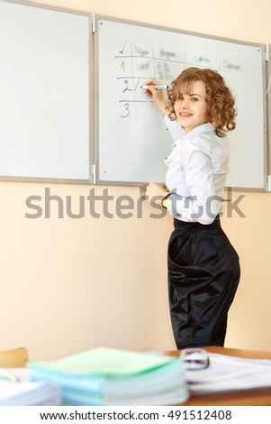 teacher stands at the blackboard and writing in the classroom
