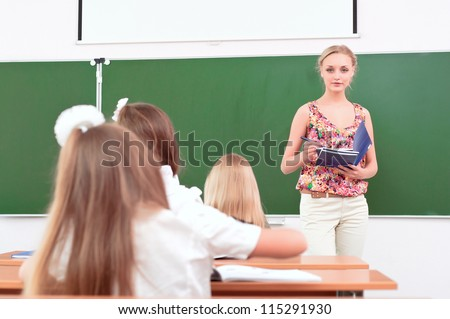 teacher stands in front of students in the class - stock photo