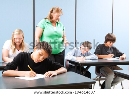 Teacher supervising high school students as they take and achievement test.