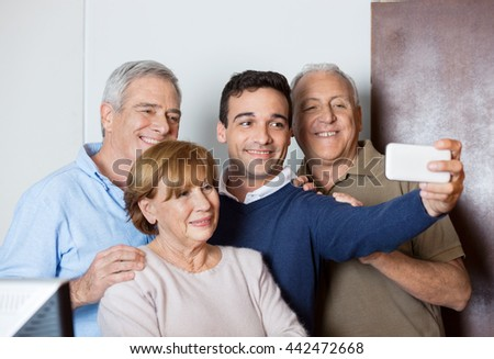 Teacher Taking Selfie With Senior Students In Computer Class - stock photo