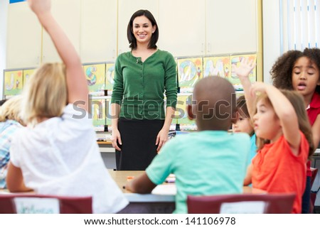 Teacher Talking To Elementary Pupils In Classroom - stock photo
