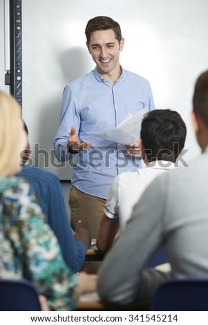 Teacher Talking To Pupils In Class - stock photo