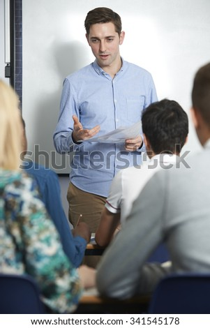 Teacher Talking To Teenage Pupils In Class - stock photo