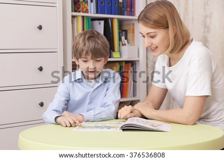 teacher teaches the pupil. Sit at the green table. Read the textbook. The show on the page. They smile - stock photo