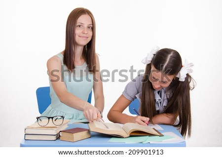 Teacher teaches the student sitting with him at the table