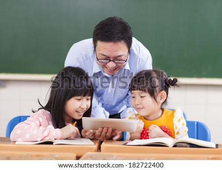 Teacher teaching  children with digital tablet or ipad - stock photo