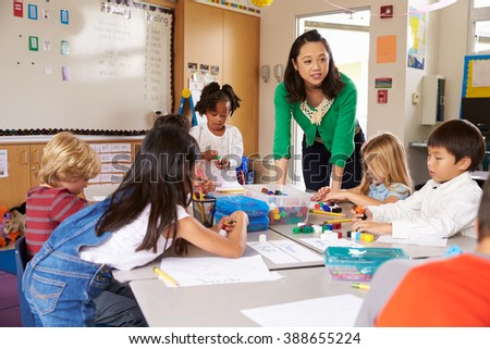 Teacher teaching elementary kids with block play in class - stock photo