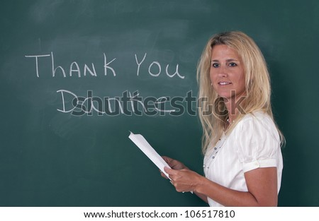 Teacher teaching foreign language by chalkboard in classroom. - stock photo