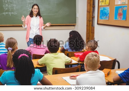 Teacher teaching her classroom of students at the elementary school - stock photo