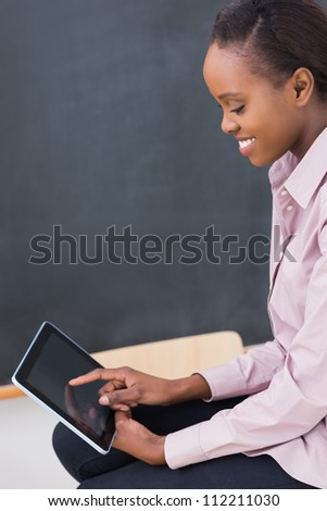 Teacher touching a tablet computer while looking it in a classroom