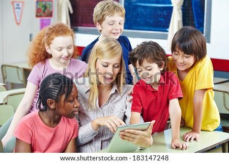 Teacher using digital media on tablet PC in elementary school class - stock photo