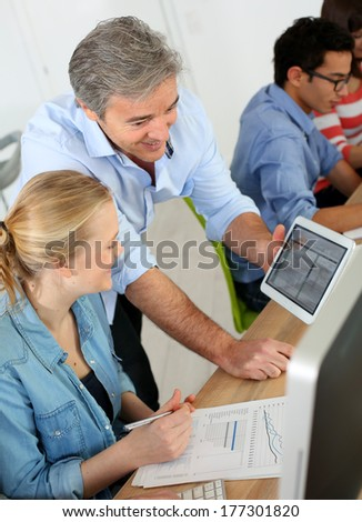 Teacher using digital tablet in school class - stock photo