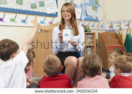 Teacher Using Number Flash Cards To Teach Maths - stock photo